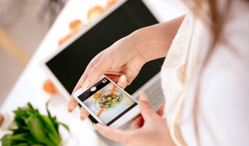 Woman holding a cell phone over a camera with a food photo on it